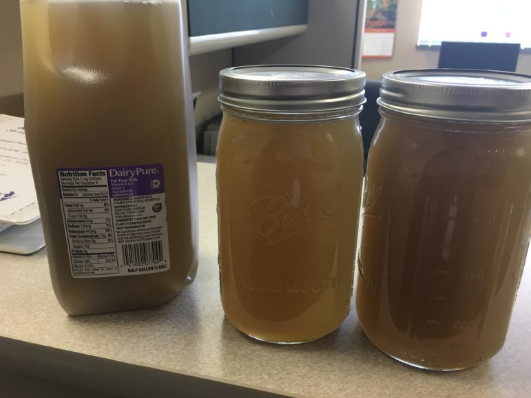 These jars contain brown water taken from a tap in Kewaunee County that researchers tied to the recent spreading of manure on a nearby field. The soil from the field and water from the home shared the same signatures for fecal contaminants. Photo courtesy of Kewaunee County Land and Water Conservation Department.