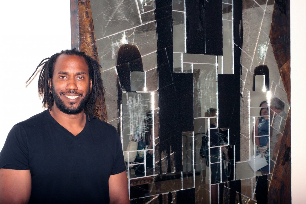 Portrait of Artist Rashid Johnson, next to his Falling Man, 2016 work made of burned red oak, black soap, wax, mirrored tile and spray enamel. Photo by Erol Reyal©