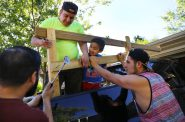 Miguel Hernandez, left, along with co-worker Pedro Tepole, center, and his cousin Eric Hernandez, build a structure on the back of Miguel's pickup truck on May 31, to help carry their belongings to Mexico. Miguel's son, Thomas Hernandez, 5, watches the construction project. Hernandez and Tepole, along with three other dairy workers, left for Mexico the following morning. Photo by Coburn Dukehart of the Wisconsin Center for Investigative Journalism.