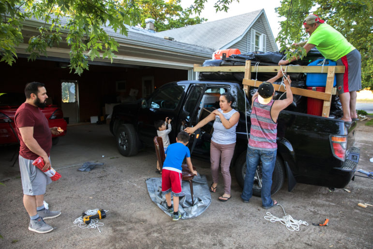 Miguel Hernandez, left, talks with his wife, Luisa Tepole, about what to load into their pickup truck as they prepare to return to their hometown in Mexico. His cousin, Eric Hernandez, and co-worker Pedro Tepole, right, help to load the truck a little after 8 p.m. on May 31. Miguel and Pedro had already worked a full-shift on the Knoepke's dairy farm in Pepin County, Wis. Photo by Coburn Dukehart of the Wisconsin Center for Investigative Journalism.