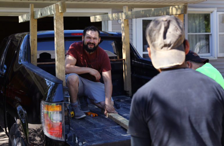 Miguel Hernandez, along with two friends, builds a structure on the back of his pickup truck on May 31, to help carry his belongings to Mexico. Photo by Coburn Dukehart of the Wisconsin Center for Investigative Journalism.