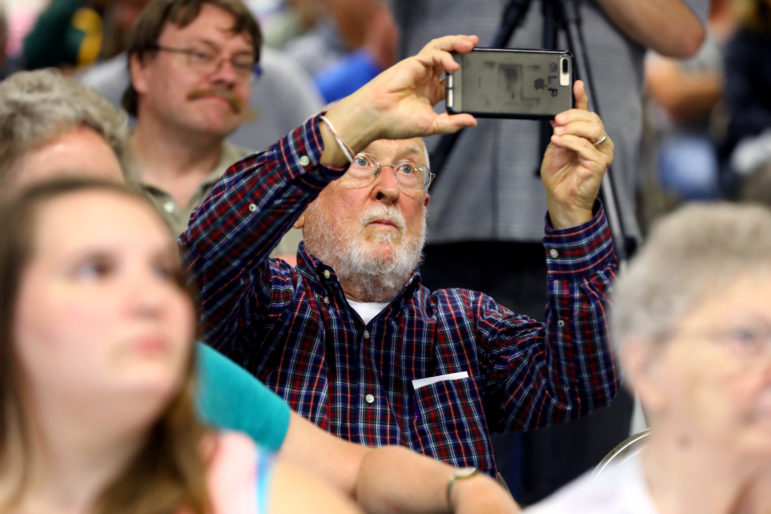 """Gerald Pellett takes a photo during a meeting. """"I'm really enthused about absorbing what was presented,"""" he said. """"Just like all good studies it brings out more questions."""" Photo by Coburn Dukehart of the Wisconsin Center for Investigative Journalism."""