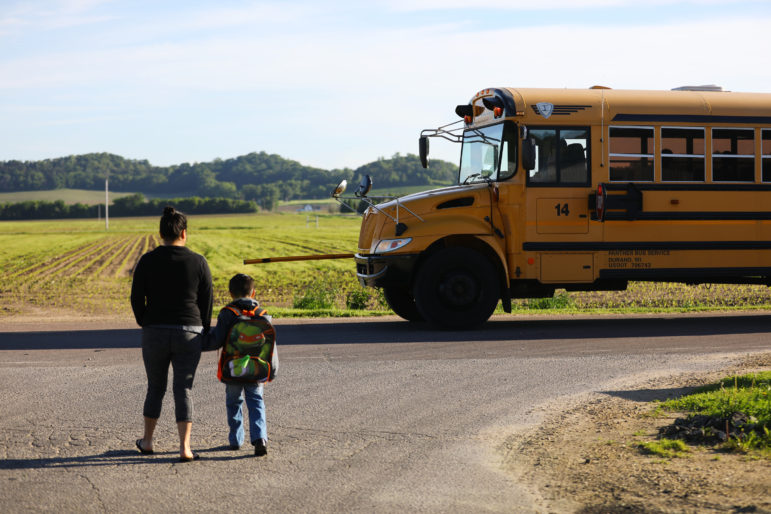 Luisa Tepole walks her son Thomas Hernandez, 5, to the bus on his last day of school in the United States on May 31. Thomas' preschool class held a graduation ceremony later that day. The rest of his classmates will enter kindergarten next fall. Thomas, who is an American citizen, flew to Mexico with his mother and brother Liam a few days later to start a new life with his family in his parents' hometown of Texhuacan, Veracruz. Photo by Coburn Dukehart of the Wisconsin Center for Investigative Journalism.