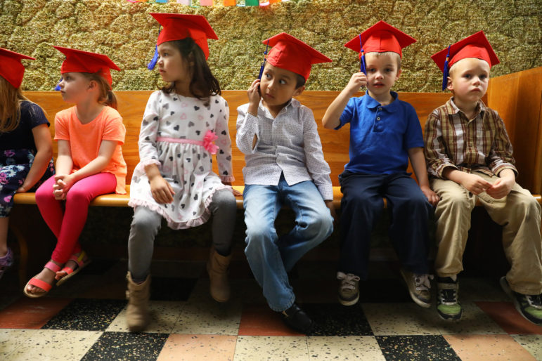 Thomas Hernandez, 5, waits in a church basement with his 4K classmates from Noah's Ark Preschool at Assumption Catholic School before their graduation ceremony on May 31. Photo by Coburn Dukehart of the Wisconsin Center for Investigative Journalism.