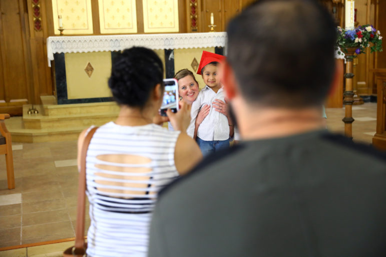 Luisa Tepole takes a photo of her son Thomas Hernandez with his preschool teacher, Angela Tulip, after the graduation ceremony for Noah's Ark Preschool at Assumption Catholic School. Miguel Hernandez stands behind her. Photo by Coburn Dukehart of the Wisconsin Center for Investigative Journalism.