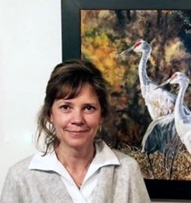 Julie Briede Ibar pictured with her painting of a group of Sandhill cranes, at the Edgewood Orchard Galleries in Fish Creek. Photo from Milwaukee County Parks.