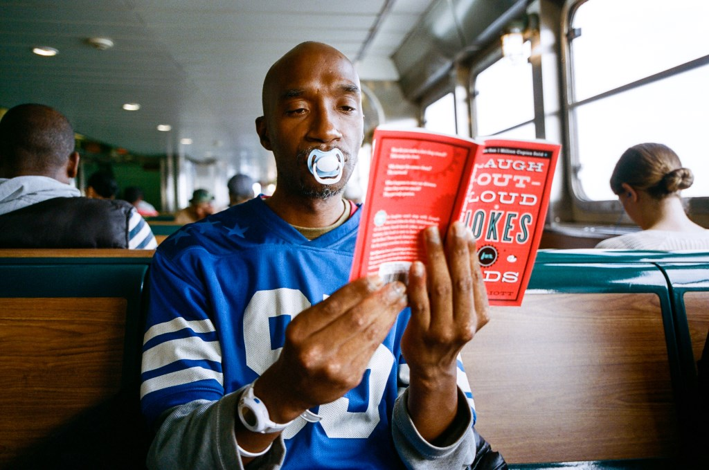 "A grown man reads at an indeterminate location with a pacifier in his mouth. The book is entitled ""Laugh-Out-Loud Jokes For Kids."" No kids are in sight. The man appears unamused. Daniel Arnold, Untitled, photographs, 2017."