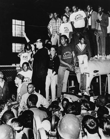 Father James Groppi and Vel Phillips stand atop the hood of a bus, surrounded by members of the Milwaukee NAACP Youth Council. Archival image from the University of Wisconsin—Milwaukee March on Milwaukee Civil Rights History Project.