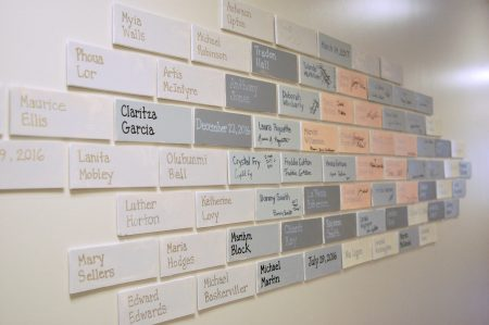 "The YWCA places a ""brick"" on the wall for each HSED graduate. Photo by Edgar Mendez."