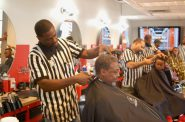 """Gaulien """"Gee"""" Smith (front, left), owner of Gee's Clippers, takes care of a customer in his barbershop. Photo by Andrea Waxman."""