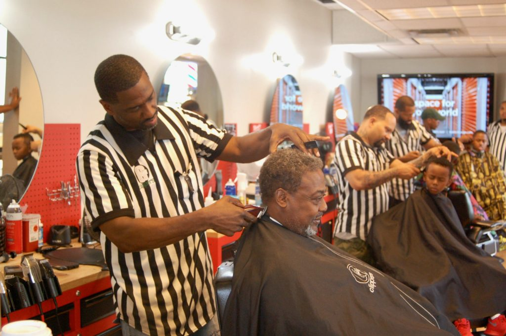 "Gaulien ""Gee"" Smith (front, left), owner of Gee's Clippers, takes care of a customer in his barbershop. Photo by Andrea Waxman."