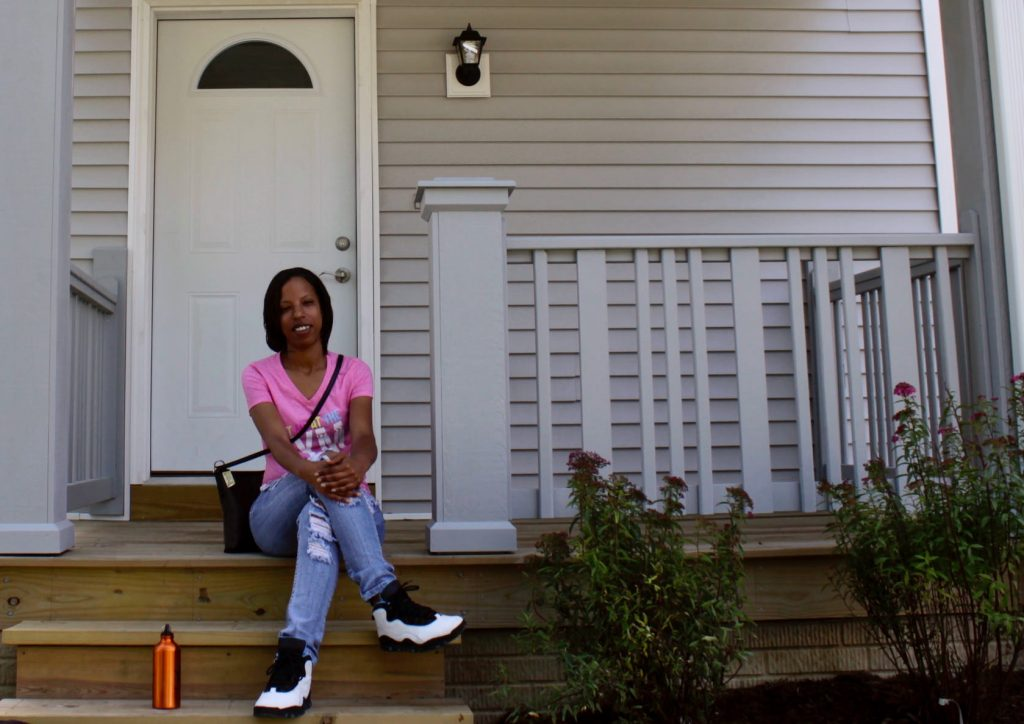 Habitat homeowner Dottie Onsager sits on the porch of her new home. Photo by Keith Schubert.