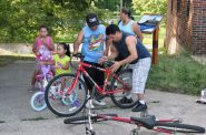 Manny Mayorga and his three children adjust their bicycles before going for a ride on the Kinnickinnic River Trail. Photo by Lydia Slattery.