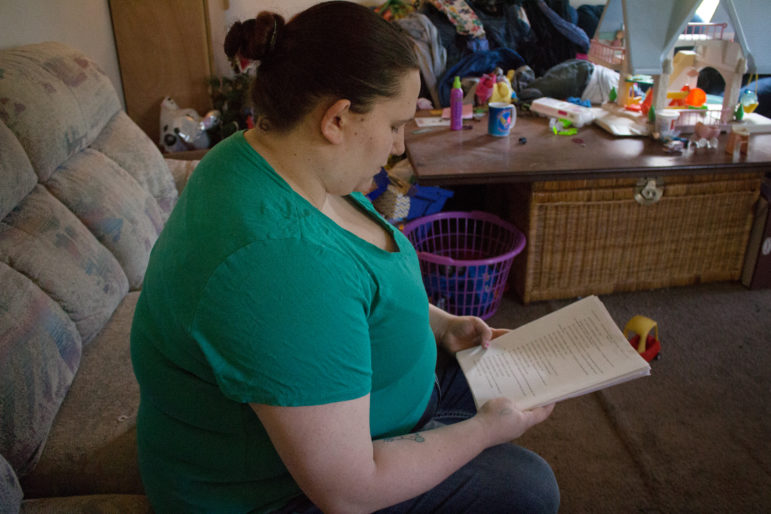 Dorothy Varallo-Speckeen looks at the transcript from her July 2013 interrogation by a Moline, Illinois, police detective about a toddler Varallo-Speckeen babysat who suffered two broken legs. After nearly two hours of being interrogated, Varallo-Speckeen admitted to the crime, which she later said she didn't commit, claiming the confession had been coerced. Photo by Krista Johnson of IowaWatch.