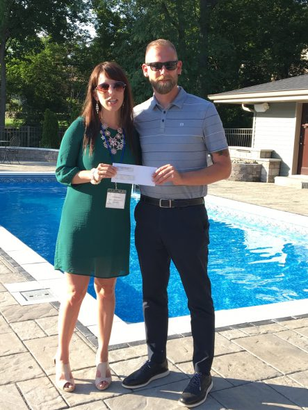 Erin Hareng, Executive Director of the Vince Lombardi Cancer Foundation, receiving the donation from Josh Brown, Milwaukee NARI President. Photo courtesy of the Milwaukee NARI.