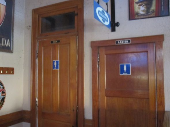 The ladies room door is smaller and of a later vintage than the adjacent men's room door. Photo by Michael Horne.