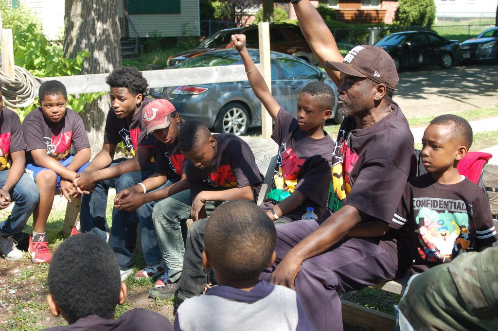 "Andre Lee Ellis meets with ""We Got This"" participants in the garden on the first Saturday of the 2015 summer program. Photo by Andrea Waxman."