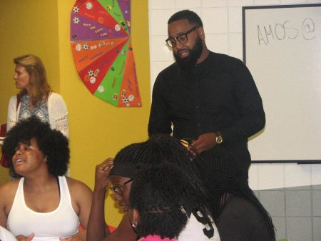 Donte Daughtry, youth program coordinator at the Mary Ryan Boys & Girls Club, helps teenagers come up with lyrics for their raps. Photo by Lydia Slattery.