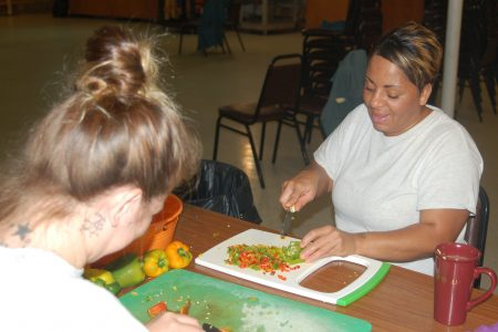 MWCC inmate Jayne Buckley chops peppers that will be packaged raw or put into prepared dishes. Photo by Andrea Waxman.