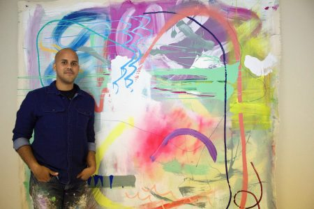Erick Ledesma displays one of his abstract pieces, which he created with acrylic, spray paint and pastels. Photo by Emmy A. Yates.