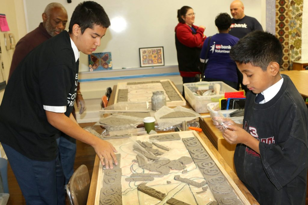 Doerfler students work on a section of a mural for the school library. Photo by Leah Harris.