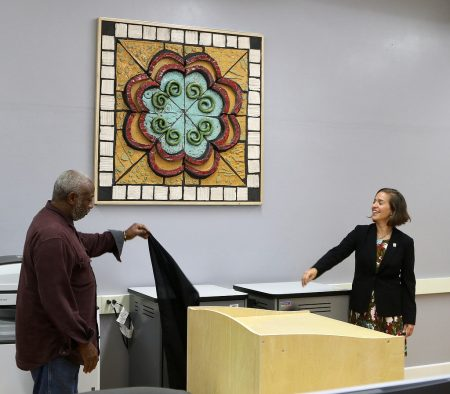 Artist Muneer Bahauddeen and Principal Jessica Quindel unveil a section of the mural. Photo by Leah Harris.