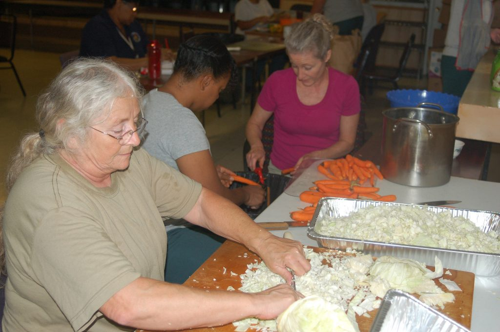 (From left) Kathy Wolfe and Iyanna Porter, inmates at Milwaukee Women's Correctional Center, prepare vegetables with Tikkun Ha-Ir volunteer Jill Goldmann Weinshel. Photo by Andrea Waxman.