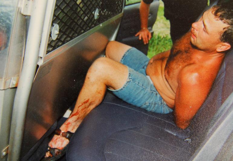 Ken Hudson is seen in the back of a police squad car after he was arrested in a June 25, 2000, murder in Kaukauna, Wis. Hudson claims the red liquid on his body was poured and smeared on him by police. Post-conviction testing of samples from his body has found either no DNA or just a sequence matching Hudson and people related to him through his mother going back many generations. (Outagamie County Sheriff's Department)
