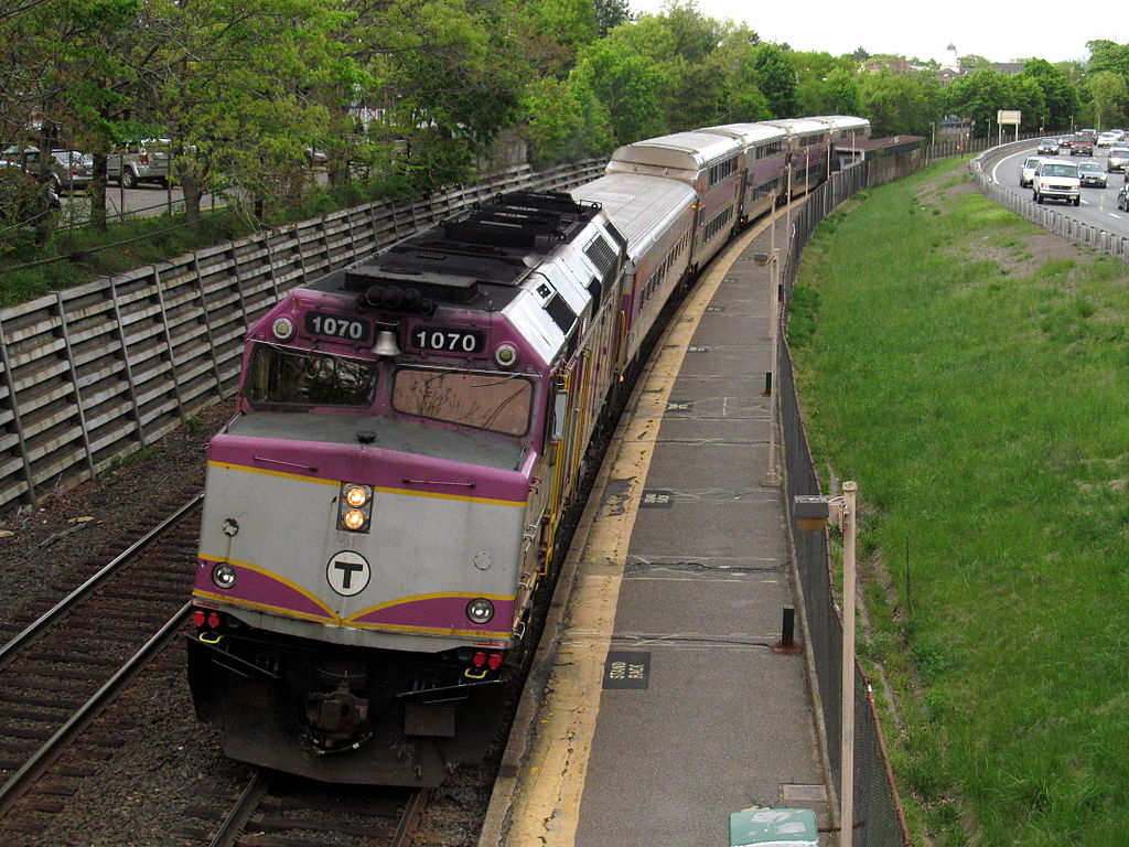 An outbound commuter rail train makes a station stop at Auburndale. View from the Woodland Road bridge. Photo by By Pi.1415926535 (Own work) [CC BY 3.0 (http://creativecommons.org/licenses/by/3.0) or GFDL (http://www.gnu.org/copyleft/fdl.html)], via Wikimedia Commons.