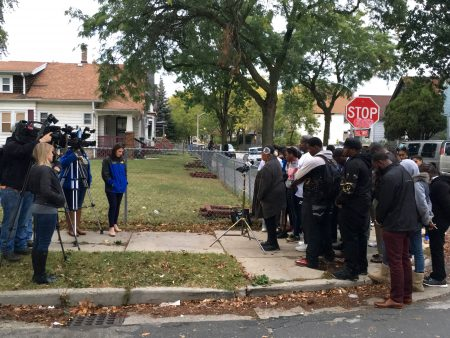 A group of about 40 community members bow their heads in prayer before beginning a news conference on Oct. 11 in the wake of the death of a 16-year-old boy from a reckless driving incident. Photo by Elliot Hughes.