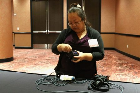 Kandi Vang preps audio equipment for an interview. Photo by Leah Harris.