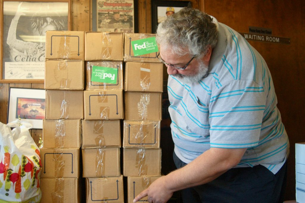 Victor Huyke, publisher of El Conquistador Latino Newspaper, takes inventory on a 5-foot stack of boxes containing handsoap bottles. Photo by Edgar Mendez.