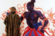 Artist Ammar Nsoroma stands with his mural painting of Shango, an Ife religion. Photo by Elizabeth Baker.