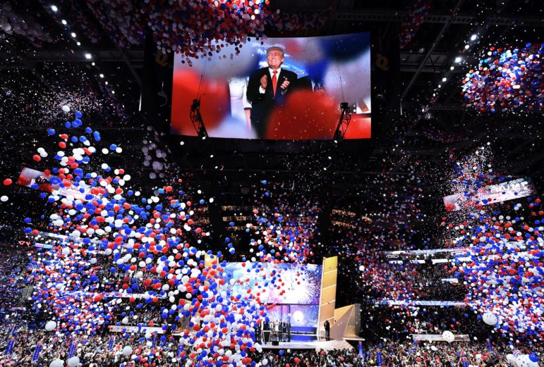 "Then-presidential candidate Donald Trump is seen onscreen at the closing of the Republican National Convention at the Quicken Loans Arena in Cleveland, Ohio, on July 21, 2016. Trump told delegates that the nation's political system ""has sold out to some corporate lobbyist for cash."" The Center for Public Integrity has learned that corporations quietly funded a posh meeting and office space at the convention. Photo by Jim Watson / AFP/Getty Images."