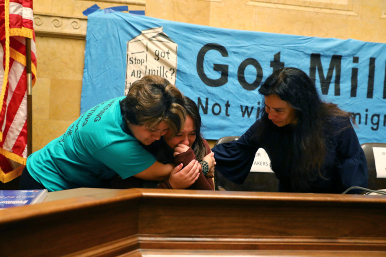 Isabel Martinez, 12, center, from Manitowoc, Wis., cries after talking about seeing her father, a dairy worker, detained and later deported when she was 7. She is comforted by Lisa Hernandez, left, and Christine Neumann-Ortiz, during a gathering at the State Capitol to protest Assembly Bill 190, the so-called sanctuary cities bill, on Sept. 27. Photo by Coburn Dukehart / Wisconsin Center for Investigative Journalism.
