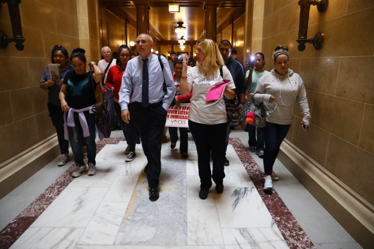 Jennifer Estrada, center right, leads a group of people through the halls of the Wisconsin State Capitol in Madison, Wis., to lobby legislators to vote against Assembly Bill 190, on Sept. 27. Estrada's former husband, a dairy worker, was deported to Mexico in 2011. Opponents argue the bill would encourage discrimination and racial profiling in the state and potentially separate Wisconsin families through deportation. Photo by Coburn Dukehart / Wisconsin Center for Investigative Journalism.