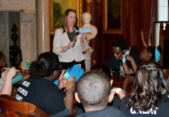 Division of Criminal Investigation Special Agent Joell Schigur speaks to a group from the Boys & Girls Club of Dane County at the State Capitol in 2013. Schigur sued the Department of Justice for alleged illegal retaliation under the whistleblower law, but lost her case at the state Supreme Court in 2015. Photo from the Wisconsin Department of Justice.