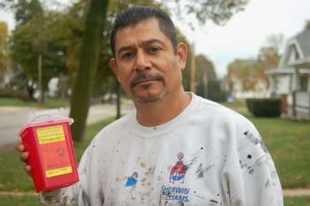 Rafael Mercado holds a container of syringes collected during a recent needle clean-up on the South Side. Photo by Edgar Mendez.