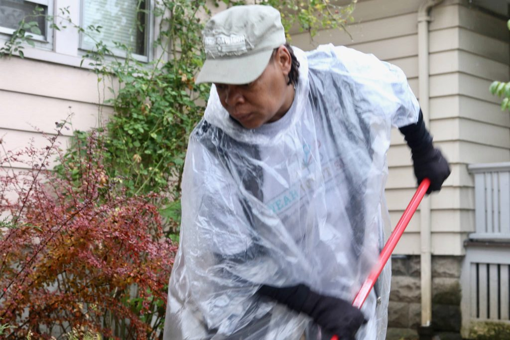Gloria Lee helps with landscaping as Revitalize Milwaukee volunteers repair her home. Photo by Leah Harris.