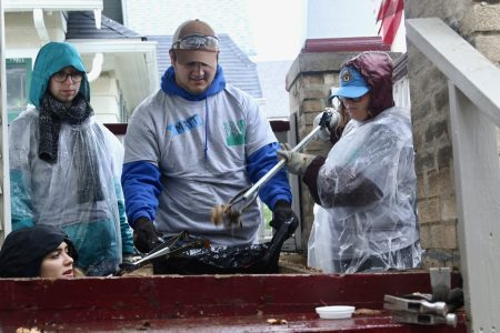 Volunteers in rain gear install a new porch during Block Build—Near West Side. Photo by Leah Harris.