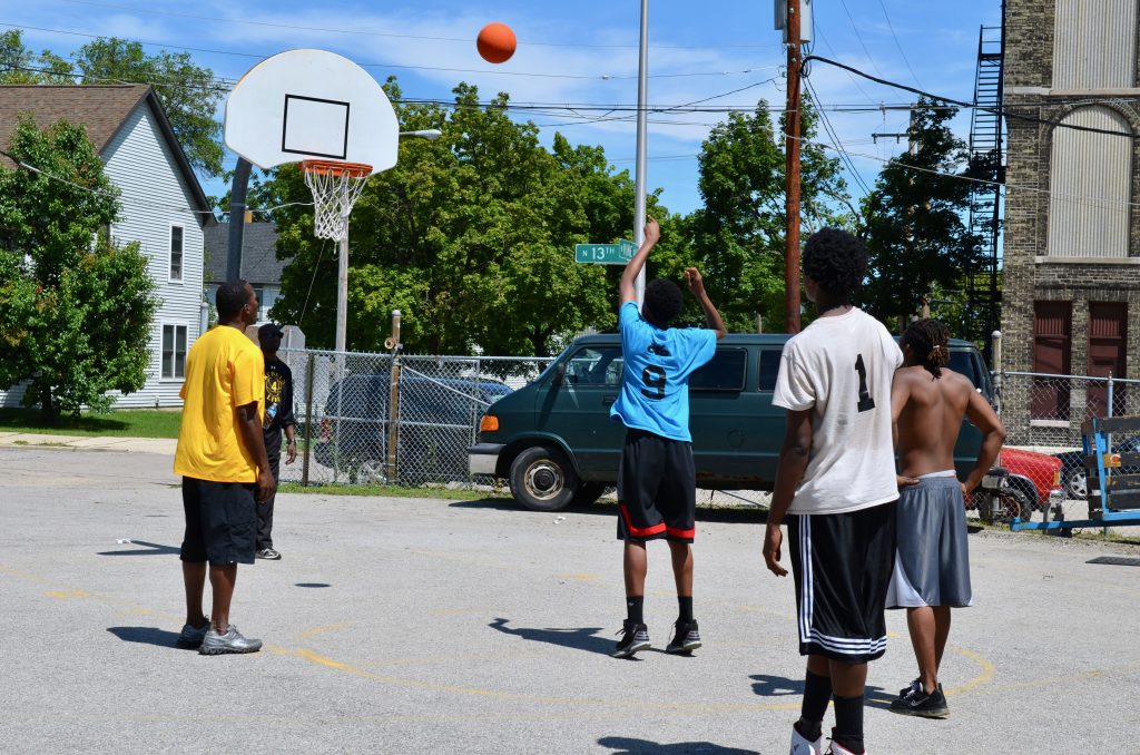 Young men play basketball at Running Rebels, one of five direct service nonprofits that received a federal grant through the city's Office of Violence Prevention. Photo by Sue Vliet.