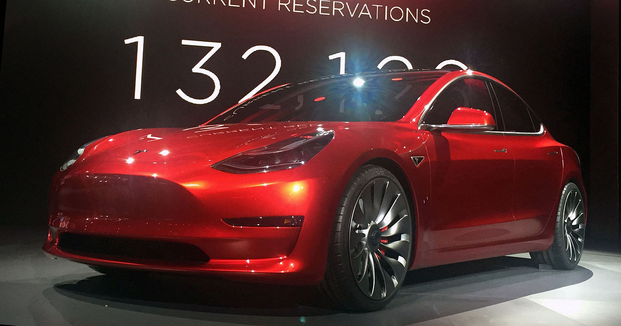 Red Tesla Model 3 at the March 31, 2016, unveiling event, Hawthorne, California. Photo by Steve Jurvetson derivative work: Smnt [CC BY-SA 4.0 (https://creativecommons.org/licenses/by-sa/4.0)], via Wikimedia Commons