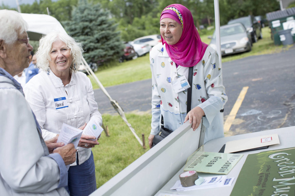 Huda Akaff, founder and director of Wisconsin Green Muslims, speaks with sister Caryl Hartjes, a member of the congregation of sisters of St. Agnes, who have installed about 800 solar panels already and halved their electric bill, and Karen Ingvoldstad, about solar energy at the Interfaith Dialogue held at the Fox Valley Islamic Society on Aug. 6, 2017 in Neenah, Wis. Photo by Michelle Kanaar.