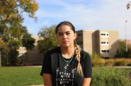 "Mariah Skenandore is a co-president of Wunk Sheek, a Native American student group at the University of Wisconsin-Madison. She is a member of the Oneida and Bad River tribes. She poses here at a sacred fire circle near Dejope Residence Hall on the UW-Madison campus, where on Oct. 9 — Indigenous Peoples' Day — graffiti that read ""Columbus Rules 1492"" was written in red paint. Photo by Riley Vetterkind/Wisconsin Center for Investigative Journalism."