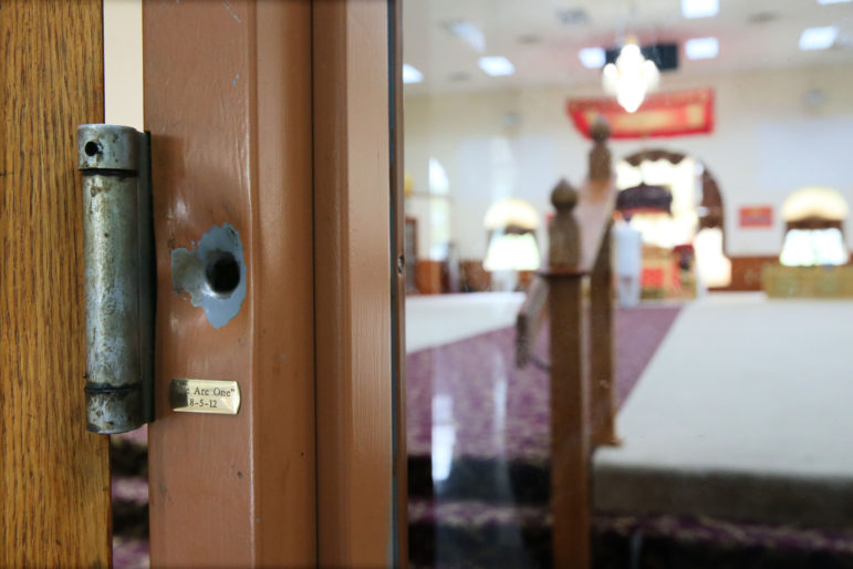"A bullet hole left from the Aug. 5, 2012, attack on the Sikh Temple of Wisconsin remains next to a hinge on the door to the main hall. Beneath the hinge is a small brass plate inscribed, ""We Are One"" with the date, 8-5-12, memorializing the mass shooting that took place there. Photo by Michael Sears / Milwaukee Journal Sentinel."
