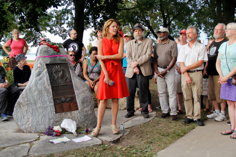 """State Rep. Chris Taylor, D-Madison, speaks to a crowd gathered around a monument dedicated to veterans who fought fascists in the Spanish Civil War, and steps away from the Gates of Heaven synagogue in Madison, Wis. This peace vigil on Sept. 20, 2017 took place on the first night of Rosh Hashanah, the Jewish New Year, and less than a day after vandals spray-painted swastikas, """"TRUMP RULES"""" and """"ANTIFA SUCKS"""" in large red letters on the face of the monument. Photo by Alexandra Hall / WPR/Wisconsin Center for Investigative Journalism."""