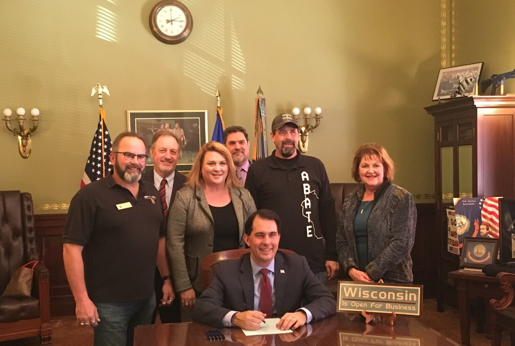 Rep. Janel Brandtjen stands behind Gov. Scott Walker as he prepares to sign AB-201. The Bike Fed's Dave Cieslewicz is behind her and to her left. Photo courtesy of the Bike Fed.