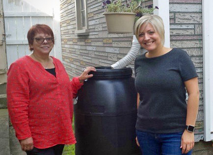 Participants in a 2016 Cool Choices program at Follett Corporation show off their rain barrel.