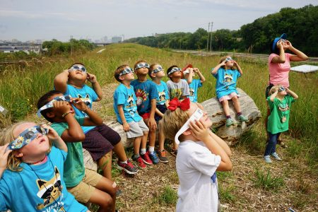Summer campers from the Menomonee Valley Urban Ecology Center observe the eclipse in Three Bridges Park. Photo by Adam Carr.