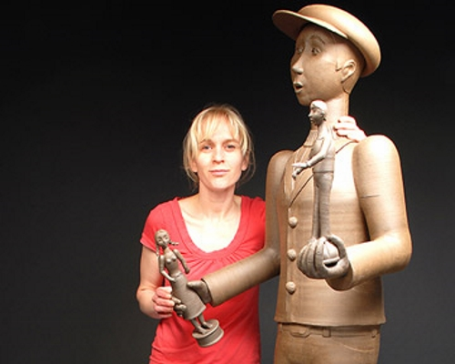 Gerit Grimm standing next to the peddler of The Peddler and Female Shopper, Stoneware, 2011. Photo from MOWA.